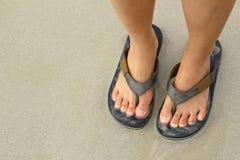 Ноги маленькой девочки в сандалиях шлоп-шлоп на море приставают к берегу Стоковая Фотография