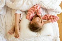 Ноги маленькой девочки и сестер на подушке на кровати Стоковые Изображения