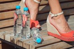 Ноги маленькой девочки с бутылки воды на стенде Стоковое Изображение RF