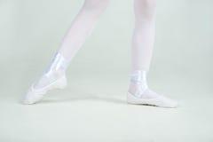 Ноги маленькой молодой балерины представляют на камере Стоковые Изображения RF