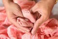 Ноги младенца в руках отца Стоковые Фото