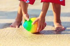 Ноги младенца идя на шарик рэгби пляжа песка хватая, шаловливый малыша нося раздувной шарик удерживания руки armbands стоковые изображения rf