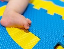 Ноги младенца на красочном поле Стоковое Изображение