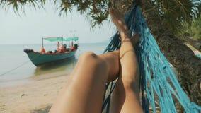 Ноги молодой женщины лежа на гамаке на песочном пляже острова в замедленном движении сток-видео