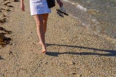 Ноги молодой женщины в конце прибоя вверх Стоковое Изображение