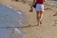 Ноги молодой женщины в конце прибоя вверх Стоковые Фотографии RF