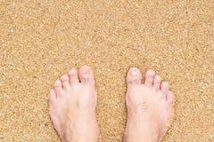 Ноги мужчины стоя на песке пляжа Стоковая Фотография