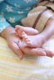 Ноги младенца в руке мамы Стоковые Изображения
