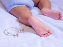 Ноги младенца на белой ткани и Anklets стоковая фотография rf