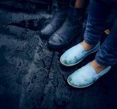 Ноги на мостоваой 2 девушки в средствах и резиновых ботинках стоя асфальт в дожде Конец-вверх Стоковая Фотография