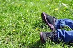 Ноги на траве, предпосылке травы, траве в солнечном свете, части  Стоковая Фотография