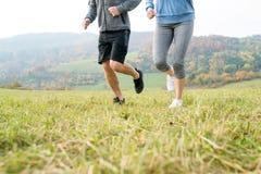 Ноги непознаваемых пар бежать в природе осени Стоковые Фото