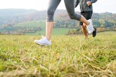Ноги непознаваемых пар бежать в природе осени Стоковая Фотография