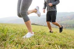 Ноги непознаваемых пар бежать в природе осени Стоковое Изображение