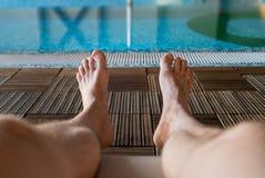 Ноги парня на предпосылке крытого бассейна Стоковая Фотография RF