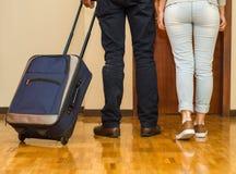 Ноги пар нося вскользь брюки идя к двери вытягивая голубой чемодан, концепцию гостя общежития Стоковое Изображение RF