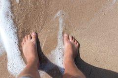 Ноги персоны на песке Ноги человека стоя на ионе песка пляж сверху Горизонтальная съемка outdoors тюкованный Стоковые Фото