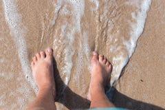 Ноги персоны на песке Ноги человека стоя на ионе песка пляж сверху Горизонтальная съемка outdoors тюкованный Стоковая Фотография RF