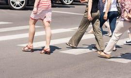 Ноги пешеходов пересекая дорогу Стоковые Изображения