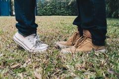 Ноги подруги стоя на цыпочках близко к парню внешнему Стоковые Изображения RF