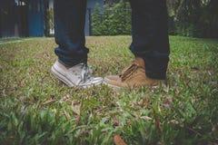 Ноги подруги стоя на цыпочках близко к парню внешнему Стоковое Изображение RF