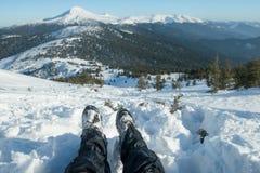 Ноги путешественника в пеших ботинках с гетрами снега в снежных горах Стоковое Изображение RF
