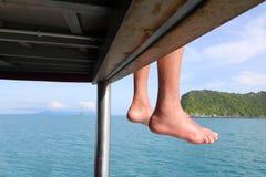 Ноги путешественника на шлюпке путешествия, люди сидя на шлюпке Стоковые Фотографии RF