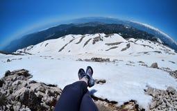 Ноги путешественника сидя на высокой горе покрывают в перемещении, Турции Стоковое Изображение