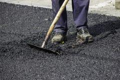 Ноги работника асфальта во время работ возобновлением дороги Стоковая Фотография RF