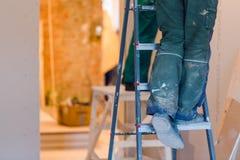 Ноги работника с зеленым workwear на лестнице Работник делает гипсокартон штукатурной плиты для стен гипса в квартире Стоковое фото RF