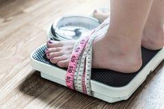 Ноги связанные вверх с измеряя лентой к масштабу веса стоковые изображения