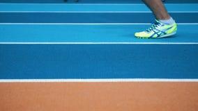 Ноги спортсмена нося ботинки спорт на бежать-следе r видеоматериал