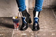 Ноги стоять на серой предпосылке с коктеилем Стоковое Изображение RF