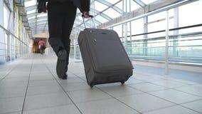 Ноги успешного бизнесмена бежать в зале терминала и вытягивая чемодан на колесах Камера следовать к молодому человеку видеоматериал