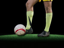 Ноги футболиста пиная шарик на черной предпосылке стоковая фотография