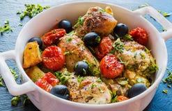 Ноги цыпленка с картошками, томатами вишни и черными оливками Белое блюдо выпечки на темной каменной предпосылке Стоковая Фотография RF