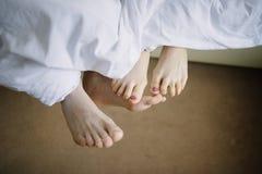 Ноги человека и женщины в конце-вверх кровати стоковые изображения