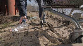Ноги человека конца-вверх бездомные принимая пластичную бутылку видеоматериал