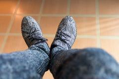 Ноги человека который носит серые ботинки с картиной a нашивок стоковое фото