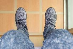 Ноги человека который носит серые ботинки с картиной a нашивок стоковые фотографии rf