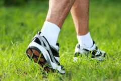 Ноги человека в идущих ботинках, который нужно шагнуть на траву Стоковое фото RF
