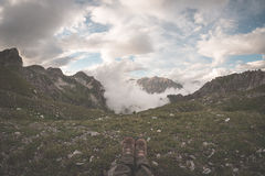 Ноги человека при пешие ботинки лежа на траве вверху высокогорная долина при сценарные облака накаляя на заходе солнца Ослабьте п Стоковые Изображения