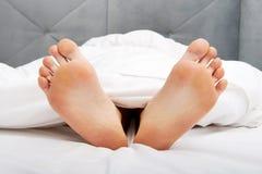 Ноги чуть-чуть женщины в спальне Стоковые Фото