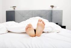 Ноги чуть-чуть женщины в спальне Стоковое фото RF