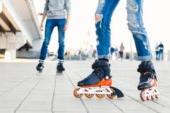 Ноги любя пар в джинсах и rollerblading езда на rolle стоковое изображение