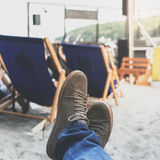 Ноги людей в тапках на предпосылке deckchairs на пляже Стоковое Изображение RF