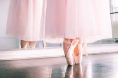 Ноги Ballerine в ботинках pointe и розовой воздушной балетной пачке обходят reflecte стоковые изображения