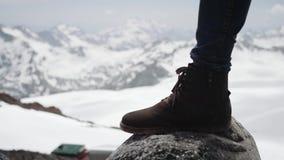 Ноги Hiker в кожаном ботинке stomps на камне на взгляде снежной горы сценарном видеоматериал