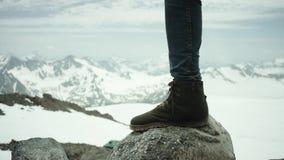 Ноги Hiker в кожаном ботинке stomps на утесе на взгляде снежной горы сценарном акции видеоматериалы