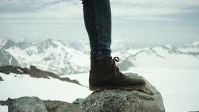 Ноги Hiker в кожаном ботинке stomps на утесе на взгляде снежной горы сценарном видеоматериал